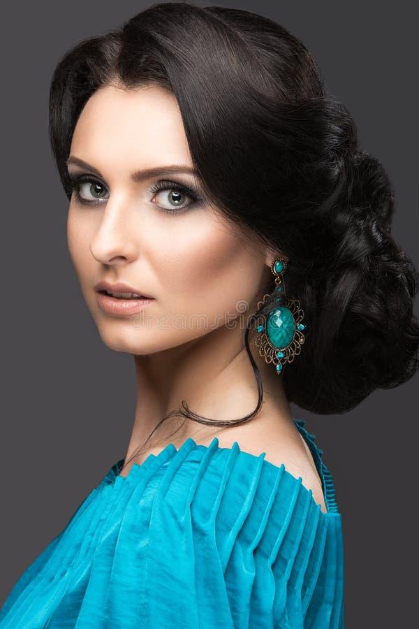 一件蓝色礼服的美丽的女孩有晚上构成和发型的 秀丽表面 免版税库存图片