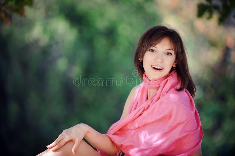 一件蓝色礼服的美丽的妇女坐一条长凳在公园 免版税库存图片