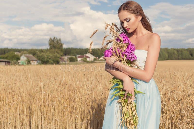 一件蓝色礼服的美丽的性感的亭亭玉立的女孩在与花和玉米穗花束的领域在他的手上在晴朗的日落 免版税库存照片