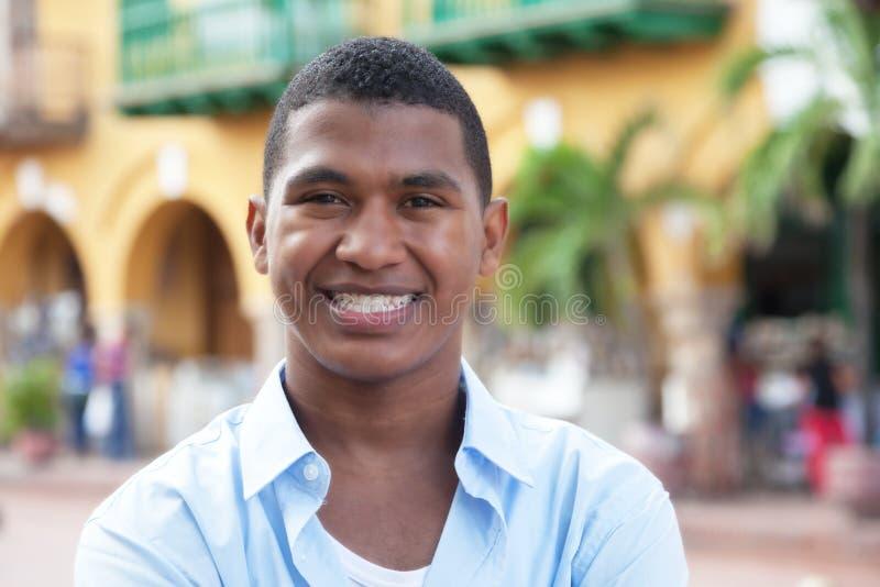 一件蓝色衬衣的愉快的人在一个五颜六色的殖民地镇 免版税库存图片