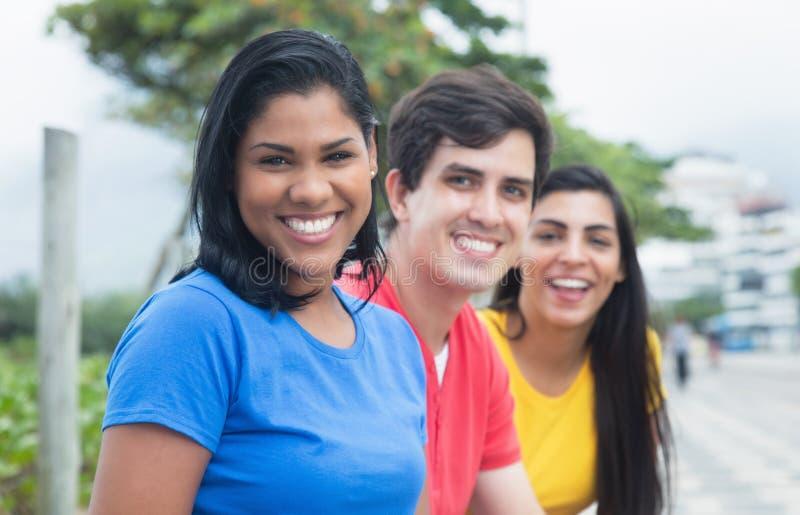 一件蓝色衬衣的美丽的拉丁妇女有白种人人和当地朋友的 库存照片