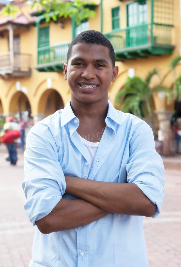 一件蓝色衬衣的英俊的人在一个五颜六色的殖民地镇 库存图片