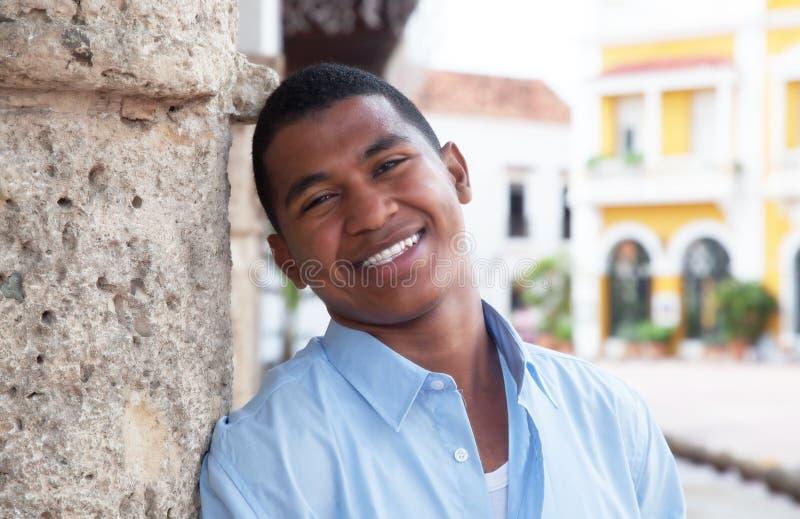 一件蓝色衬衣的年轻人在殖民地镇 库存照片