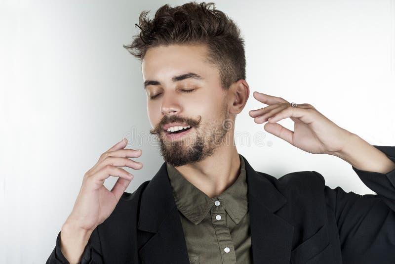 一件衬衣的时髦的人在一个美好的姿势梦想微笑 库存图片
