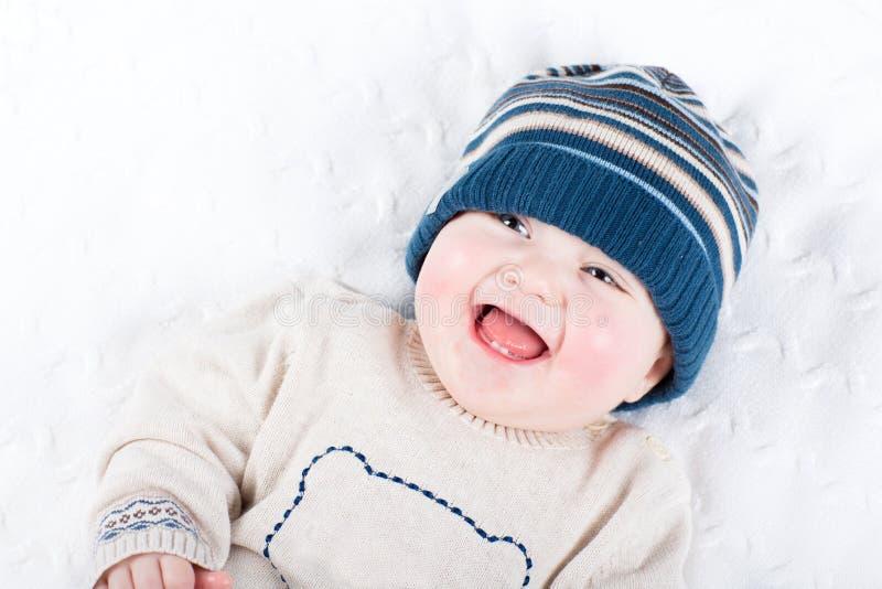 一件被编织的帽子和毛线衣的逗人喜爱的婴孩 免版税图库摄影