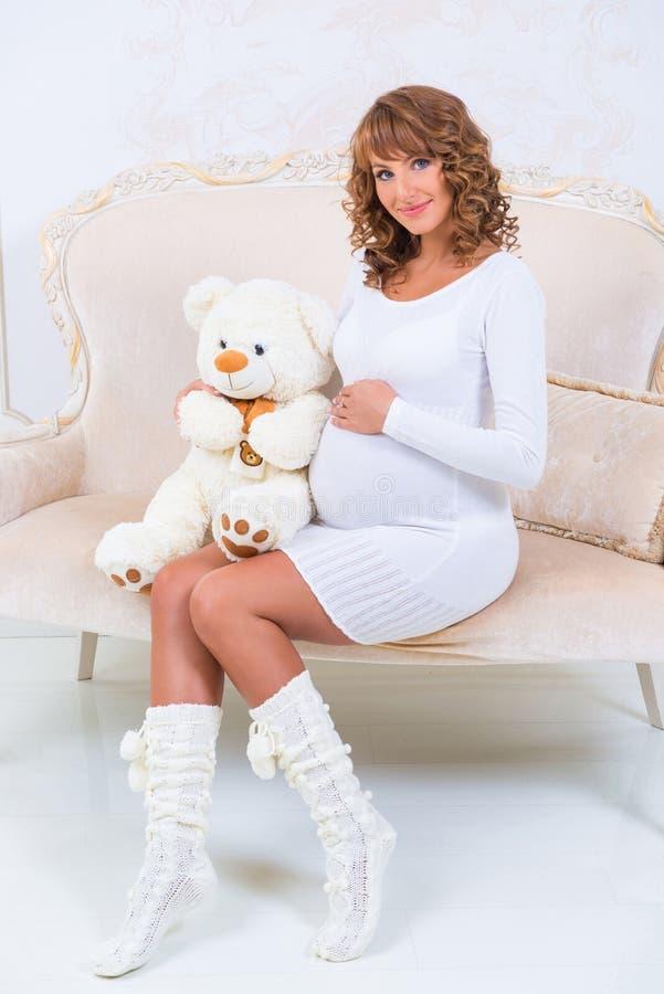 一件被编织的礼服的美丽的怀孕的女孩有玩具熊的 库存照片