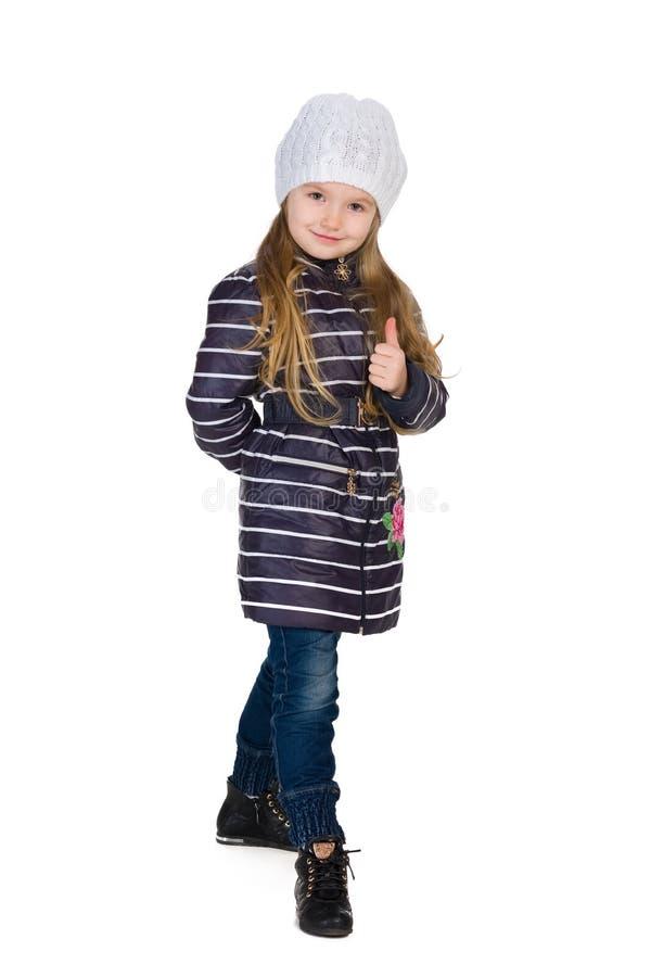一件镶边外套的小女孩举行她的赞许 库存照片