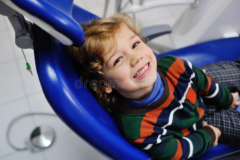 一件镶边毛线衣的逗人喜爱的婴孩在牙医的招待会 免版税库存图片