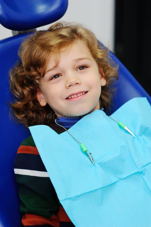 一件镶边毛线衣的逗人喜爱的婴孩在牙医的招待会 库存照片