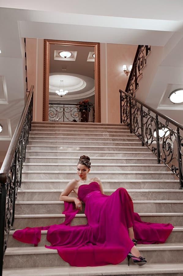 一件长的礼服的妇女坐台阶 库存照片