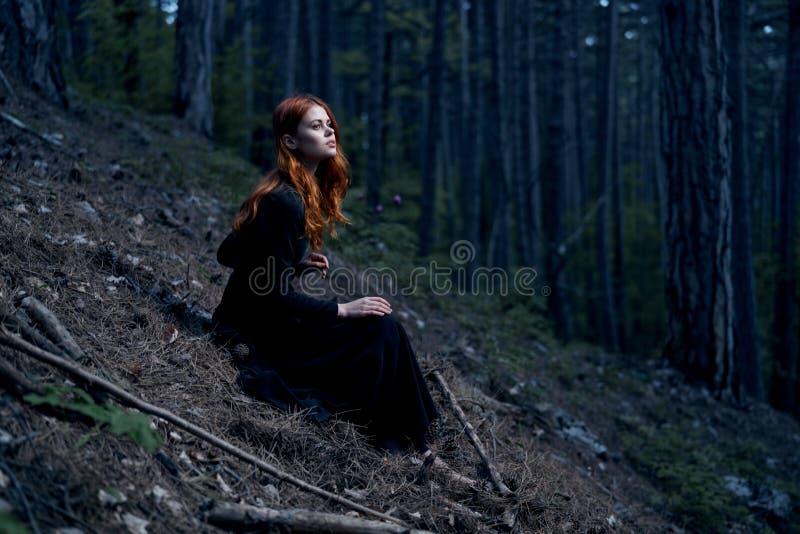 一件长的礼服的美丽的少妇在森林里 免版税库存照片