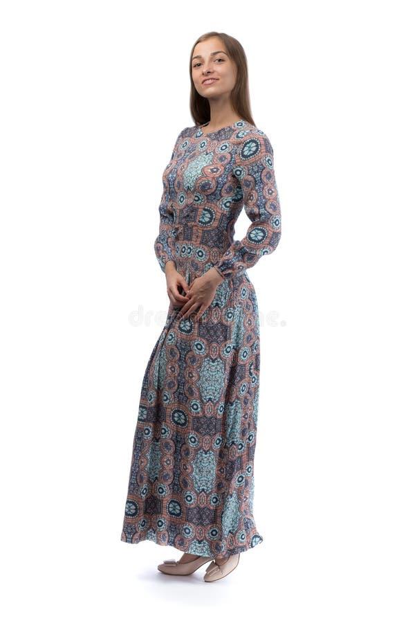 一件长的蓝色礼服的美丽的女孩在演播室 免版税库存照片