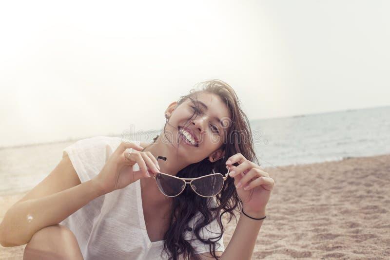 一件长袍的妇女在海滩愉快的微笑和在su放松 图库摄影