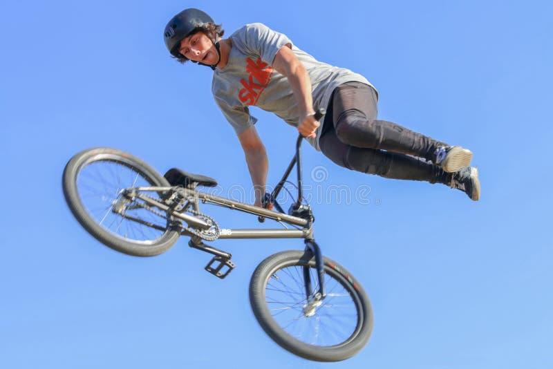 一件防护盔甲的年轻人在自行车跳 免版税库存图片