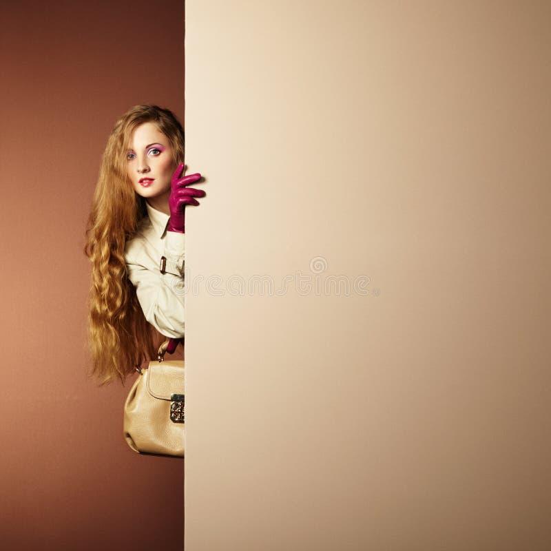 一件雨衣的照片年轻美丽的妇女在内部 免版税图库摄影