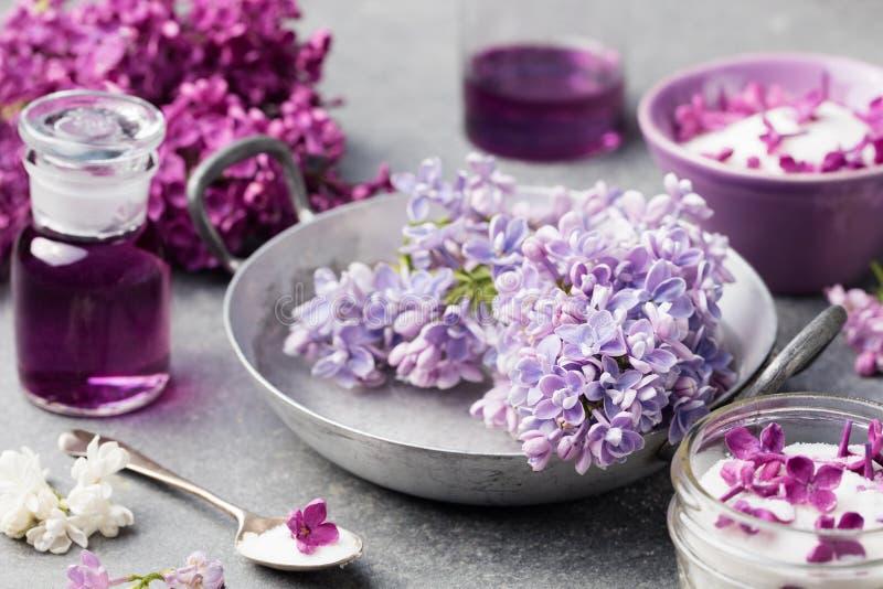 丁香开花糖和糖浆,与花开花的精油在玻璃瓶子灰色石背景中 库存照片