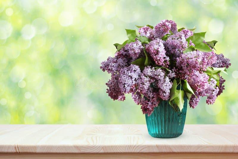 丁香花束在一张木桌上的 花瓶 库存图片