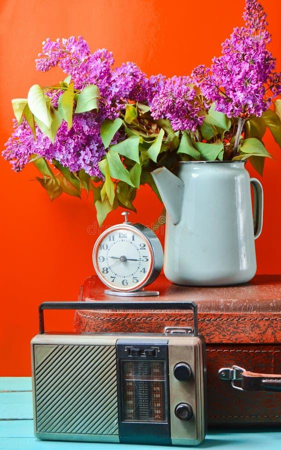 丁香花束在上釉的水壶的在古色古香的手提箱,葡萄酒收音机,在黄色背景的闹钟 减速火箭的样式静物画 免版税图库摄影