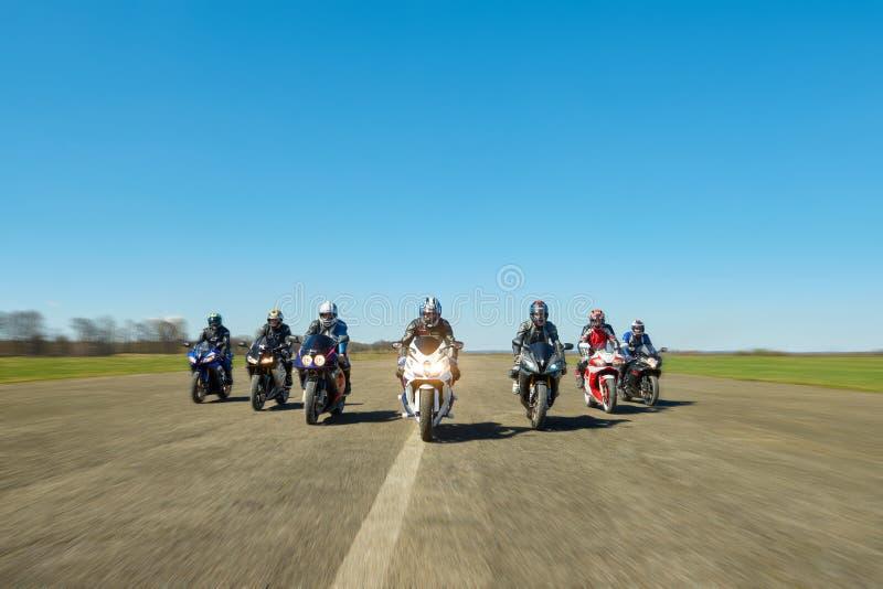 七个骑自行车的人沿领域路乘坐 免版税图库摄影