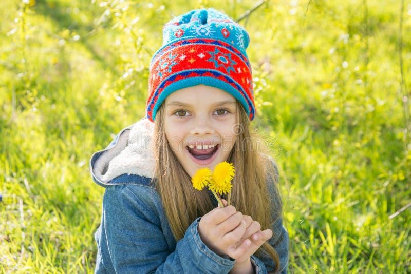 七岁的女孩在春天喜欢用开花的蒲公英 免版税图库摄影