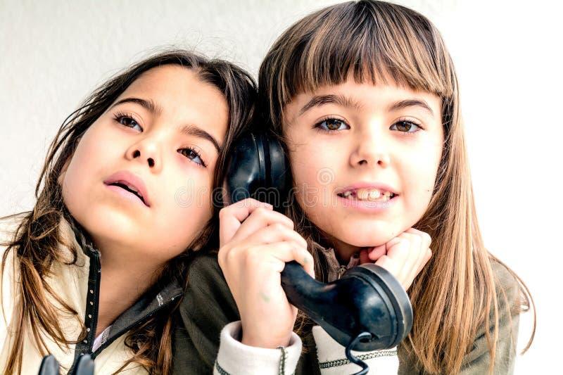 七岁的女孩谈话在老葡萄酒电话和她的sis 免版税库存图片