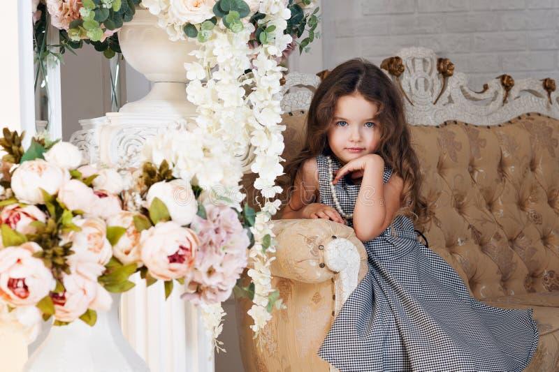 七年的一个小女孩与棕色头发的,坐在牡丹旁边花束开花,微笑,在a的一件灰色礼服 免版税库存图片
