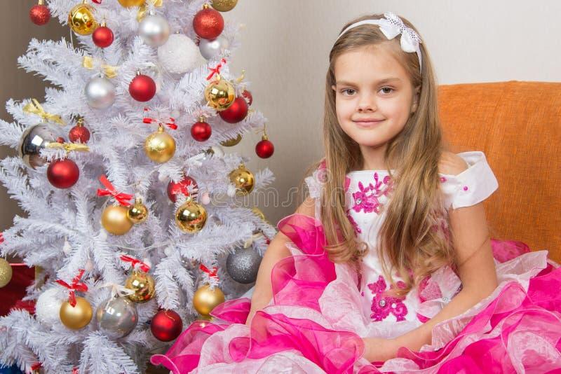 七年女孩坐在美丽的礼服的一个沙发圣诞树 图库摄影