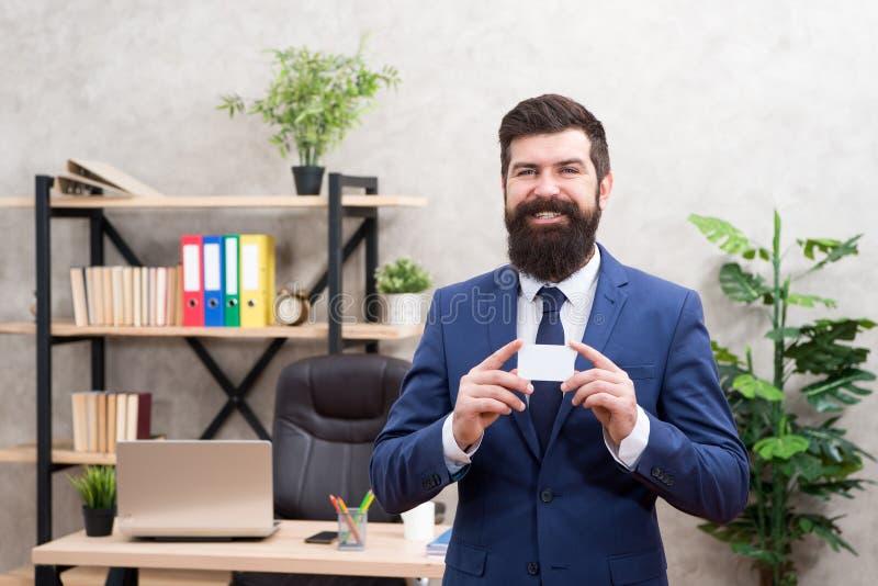 万一银行卡 财政支持 有胡子的行家总经理举行卡片 银行业务 人正装立场在办公室 免版税图库摄影
