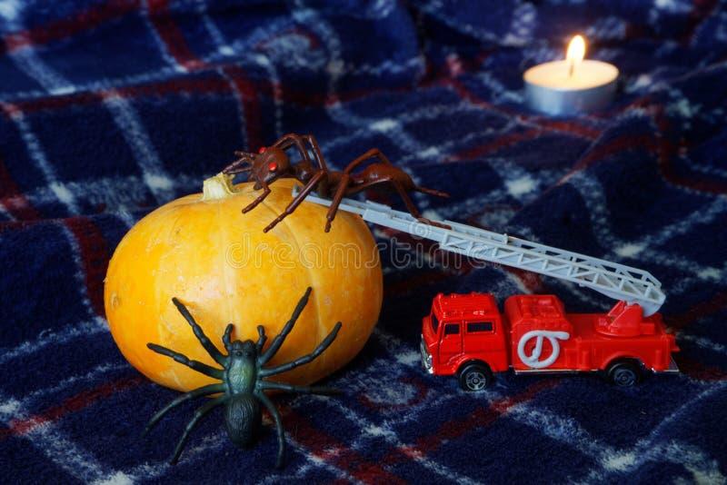 万圣夜、奇怪的昆虫和一个蜡烛的南瓜 玩具蚂蚁和 免版税库存照片