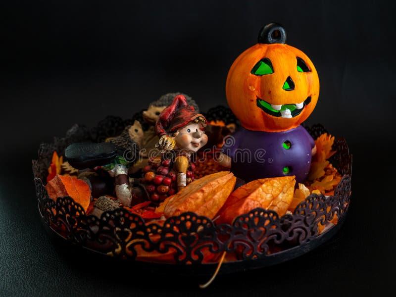 万圣夜与逗人喜爱的矮小的矮人的秋天装饰和在黑背景的被阐明的南瓜头橙色颜色 免版税图库摄影
