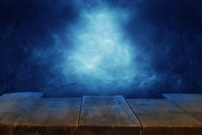 万圣夜假日概念 倒空在可怕和有薄雾的夜空背景前面的土气桌 为产品显示蒙太奇准备 库存图片