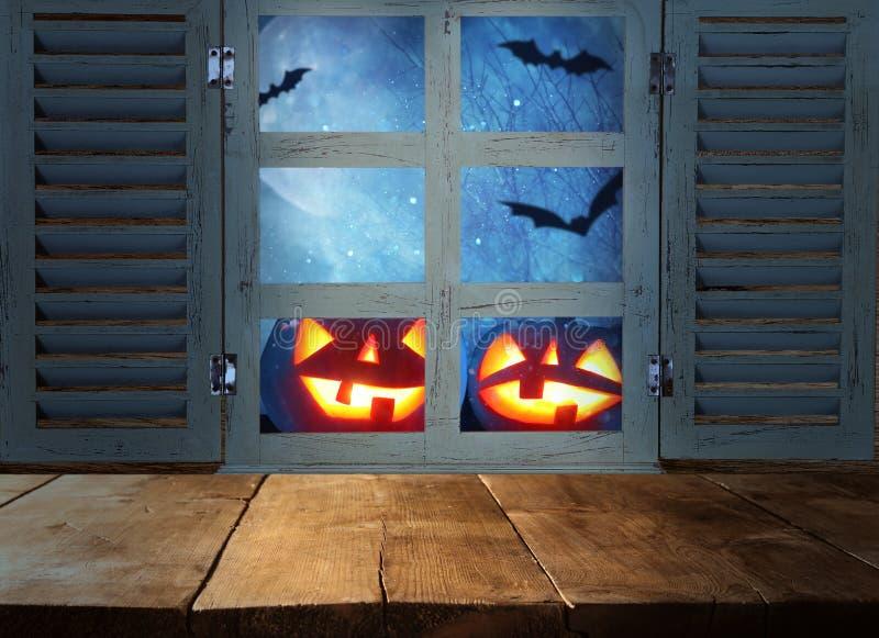 万圣夜假日概念 在被困扰的夜空背景和老窗口前面的空的土气桌 为产品显示m准备 免版税库存照片