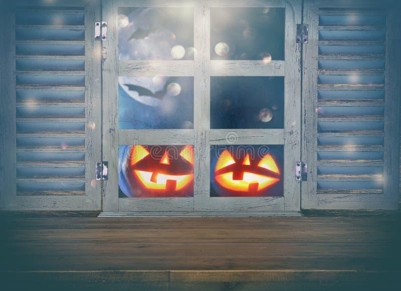 万圣夜假日概念 在被困扰的夜空背景和老窗口前面的空的土气桌 为产品显示m准备 库存图片