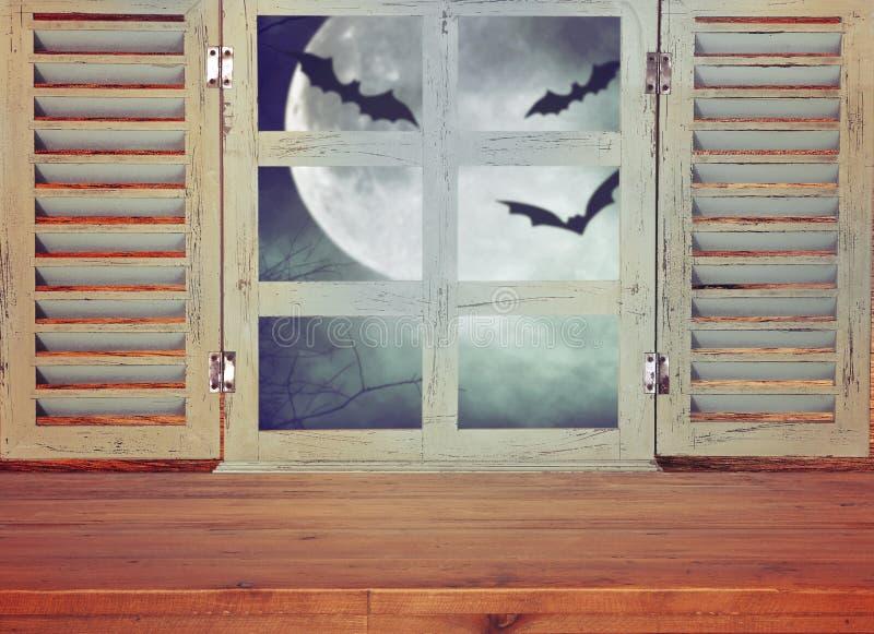 万圣夜假日概念 在被困扰的夜空背景和老窗口前面的空的土气桌 为产品显示m准备 免版税库存图片