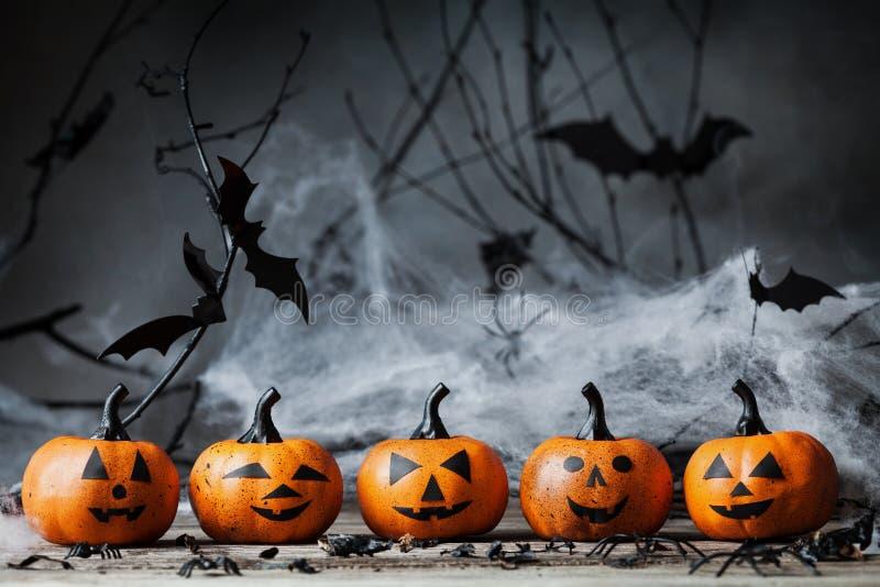 万圣夜南瓜朝向与滑稽的微笑和鬼的装饰在黑暗的木头 库存照片
