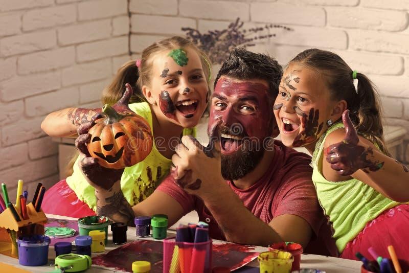 万圣夜孩子或女孩有有胡子的人父亲的拿着南瓜 库存图片