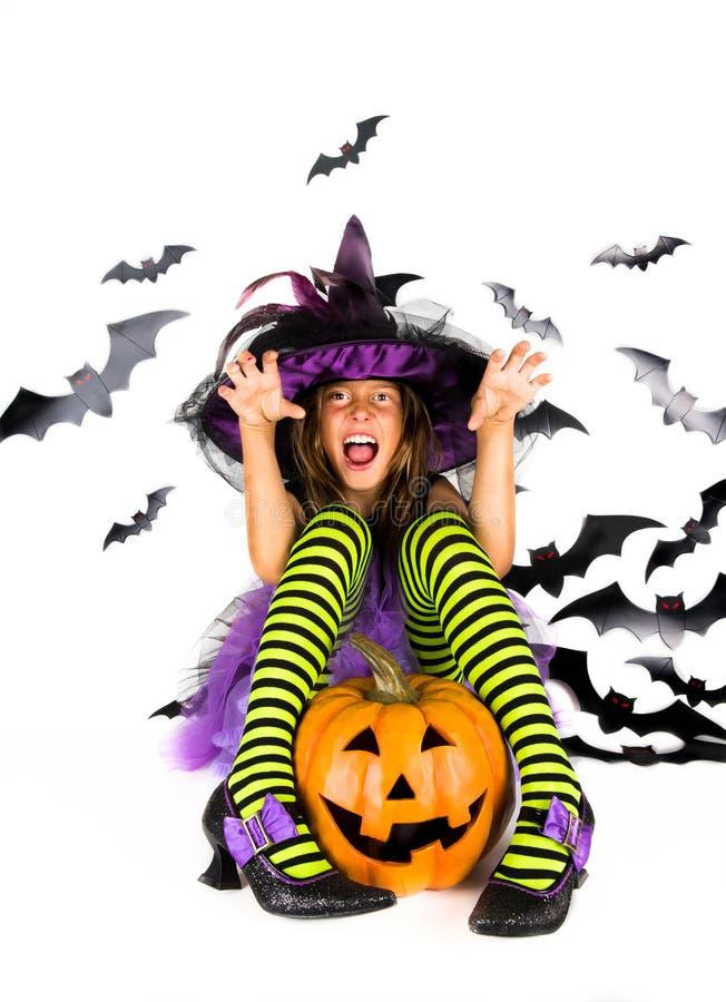 万圣夜孩子,愉快的可怕女孩在巫婆、巫师和吸血鬼南瓜补丁的德雷库拉万圣夜服装装饰了  库存图片