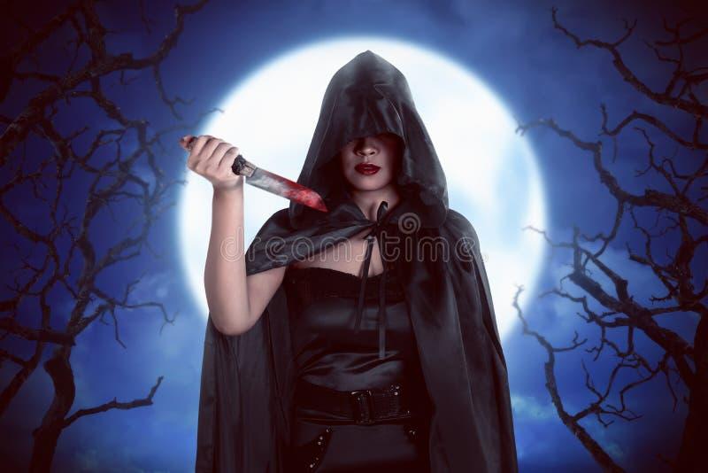 万圣夜巫婆妇女与noonlight的夜与雾backg 库存照片