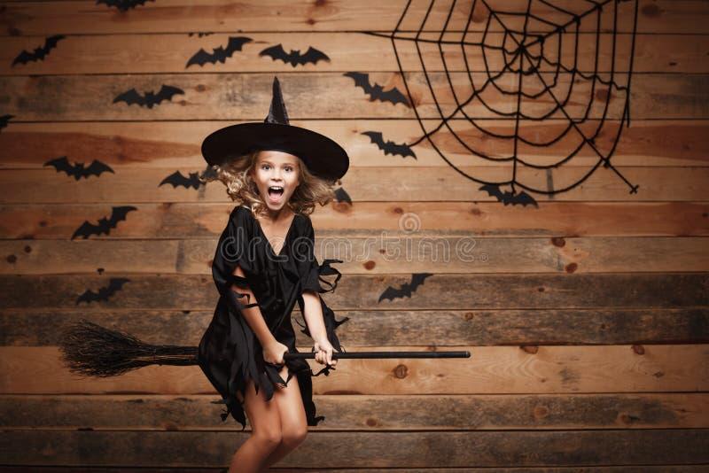 万圣夜巫婆概念-在不可思议的帚柄的小的白种人巫婆儿童飞行在棒和蜘蛛网背景 库存照片