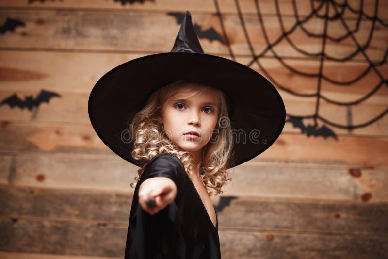 万圣夜巫婆概念-小巫婆孩子喜欢使用与不可思议的鞭子 在棒和蜘蛛网背景 免版税库存图片