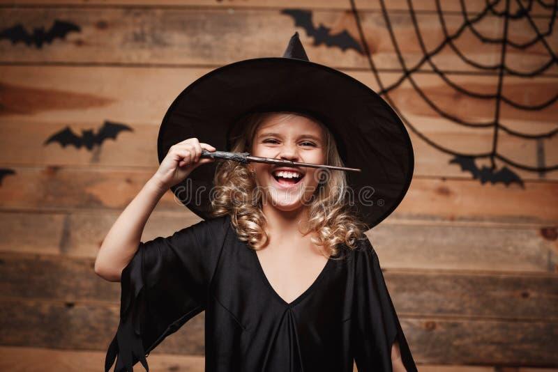 万圣夜巫婆概念-小巫婆孩子喜欢使用与不可思议的鞭子 在棒和蜘蛛网背景 免版税库存照片