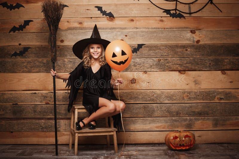 万圣夜巫婆概念-摆在与不可思议的帚柄和气球的小白种人巫婆孩子全长射击在棒和s 免版税库存图片