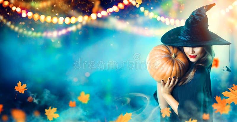万圣夜巫婆用一个被雕刻的南瓜和魔术光 免版税库存图片