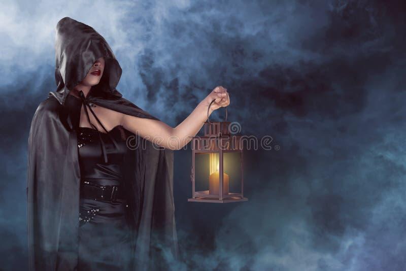 万圣夜拿着灯笼有雾背景的巫婆妇女 库存图片