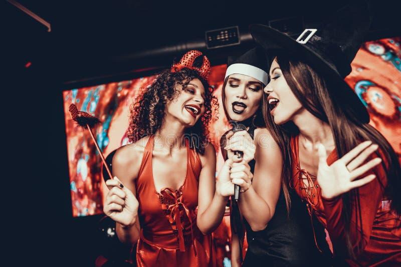万圣夜服装的少妇唱卡拉OK演唱的 库存照片