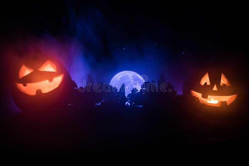 万圣夜概念用发光的南瓜 奇怪的剪影在一个黑暗的鬼的森林在晚上,神秘的风景超现实的光wi里 皇族释放例证