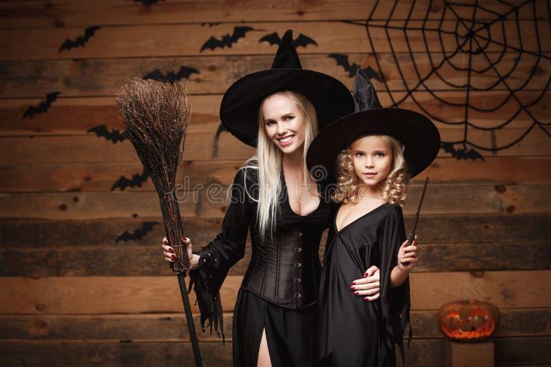 万圣夜概念-快乐的巫婆服装的庆祝万圣夜的母亲和她的女儿摆在用弯曲的南瓜在棒 免版税图库摄影