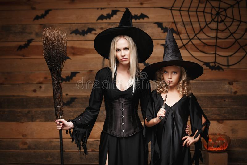 万圣夜概念-快乐的巫婆服装的庆祝万圣夜的母亲和她的女儿摆在用弯曲的南瓜在棒 库存图片