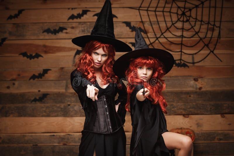 万圣夜概念-美丽的白种人有长的红色头发的在巫婆服装和不可思议的鞭子庆祝Ha的母亲和她的女儿 免版税库存图片