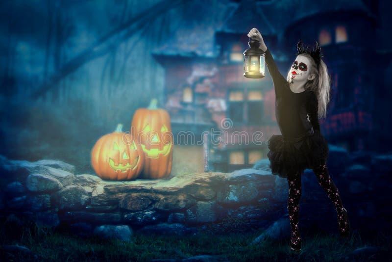 万圣夜,假日,化妆舞会概念-年轻矮小的美丽的女孩画象有头骨构成的在南瓜背景 Ha 免版税库存照片